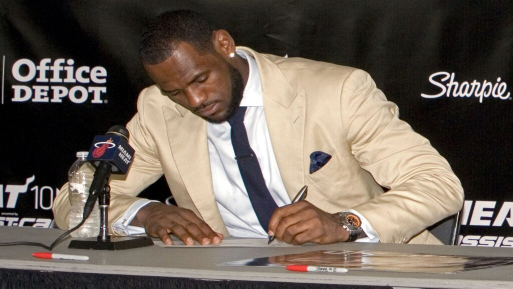 Lebron James firmando un documento con la mano izquierda